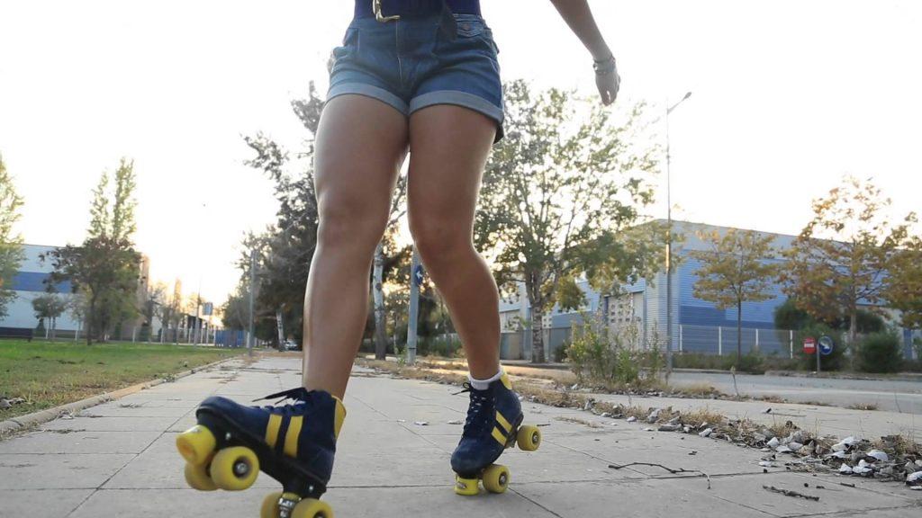 Chica con patines de 4 ruedas haciendo trucos